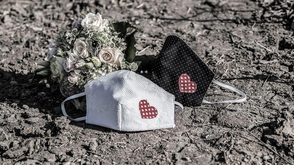 Zwei Mund-Nasen-Masken mit aufgenähtem Herz liegen neben einem Brautstrauß (Symbolbild)   Bild:pa/Fotostand