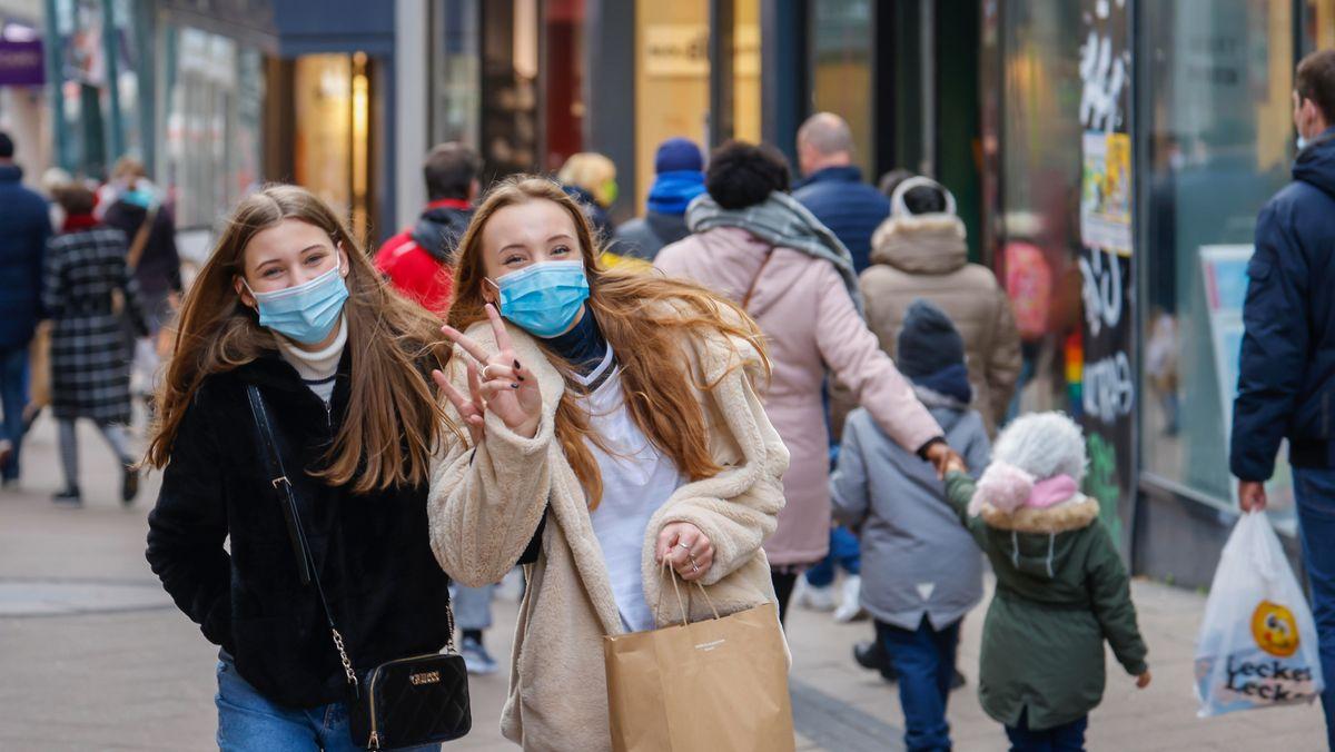 Zwei junge Frauen mit Maske in einer Einkaufsstraße