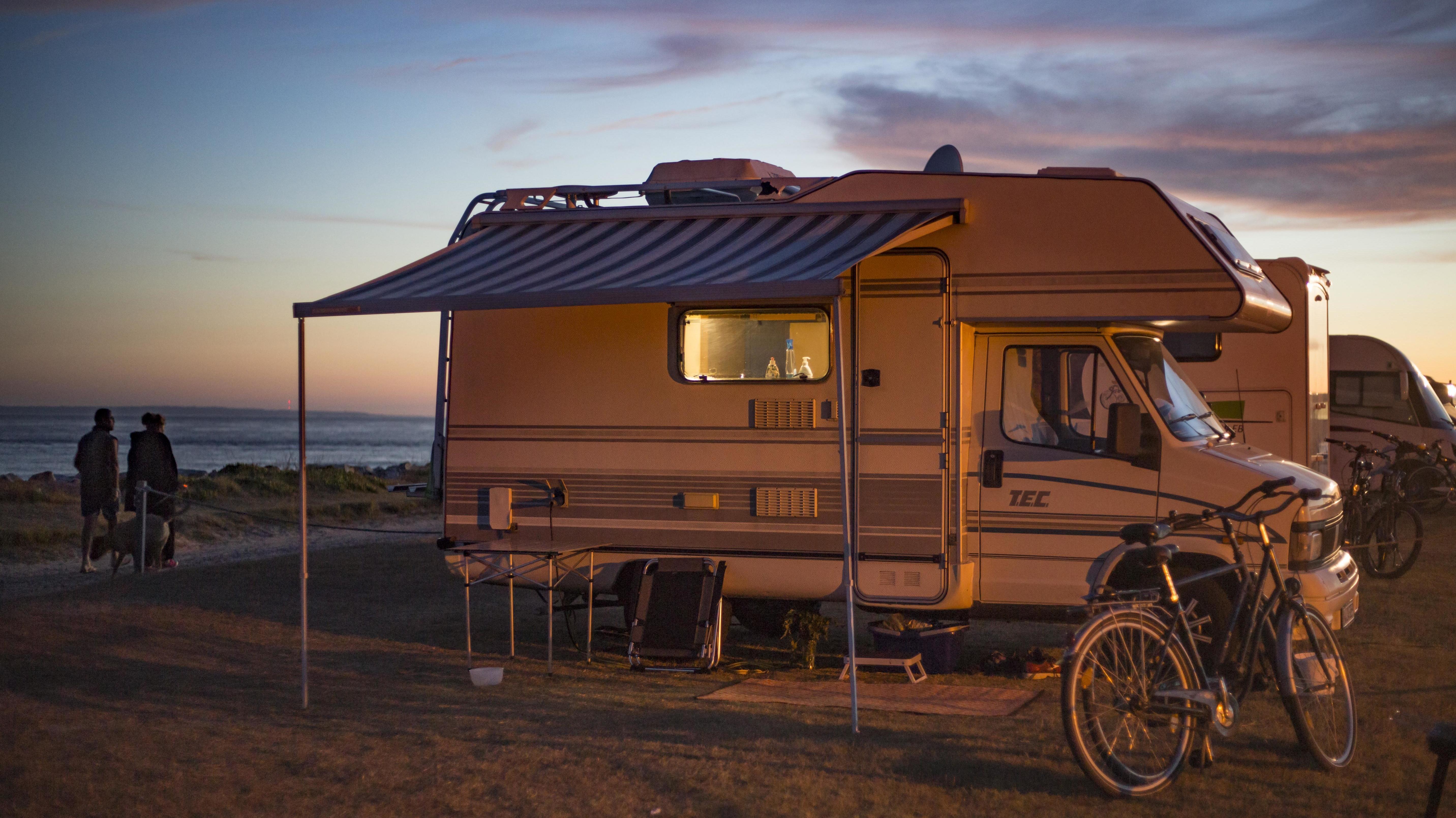Wohnmobil abends auf einem Stellplatz am Meer bei Sonnenuntergang