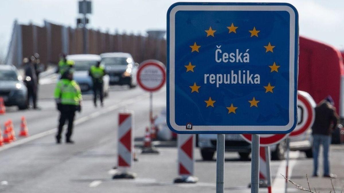 """Ein blaues Schild mit der Aufschrift """"Ceska republika"""", dahinter Grenzbeamte und wartende Autos."""