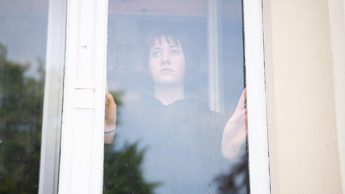 Eine Jugendliche schaut aus dem Fenster