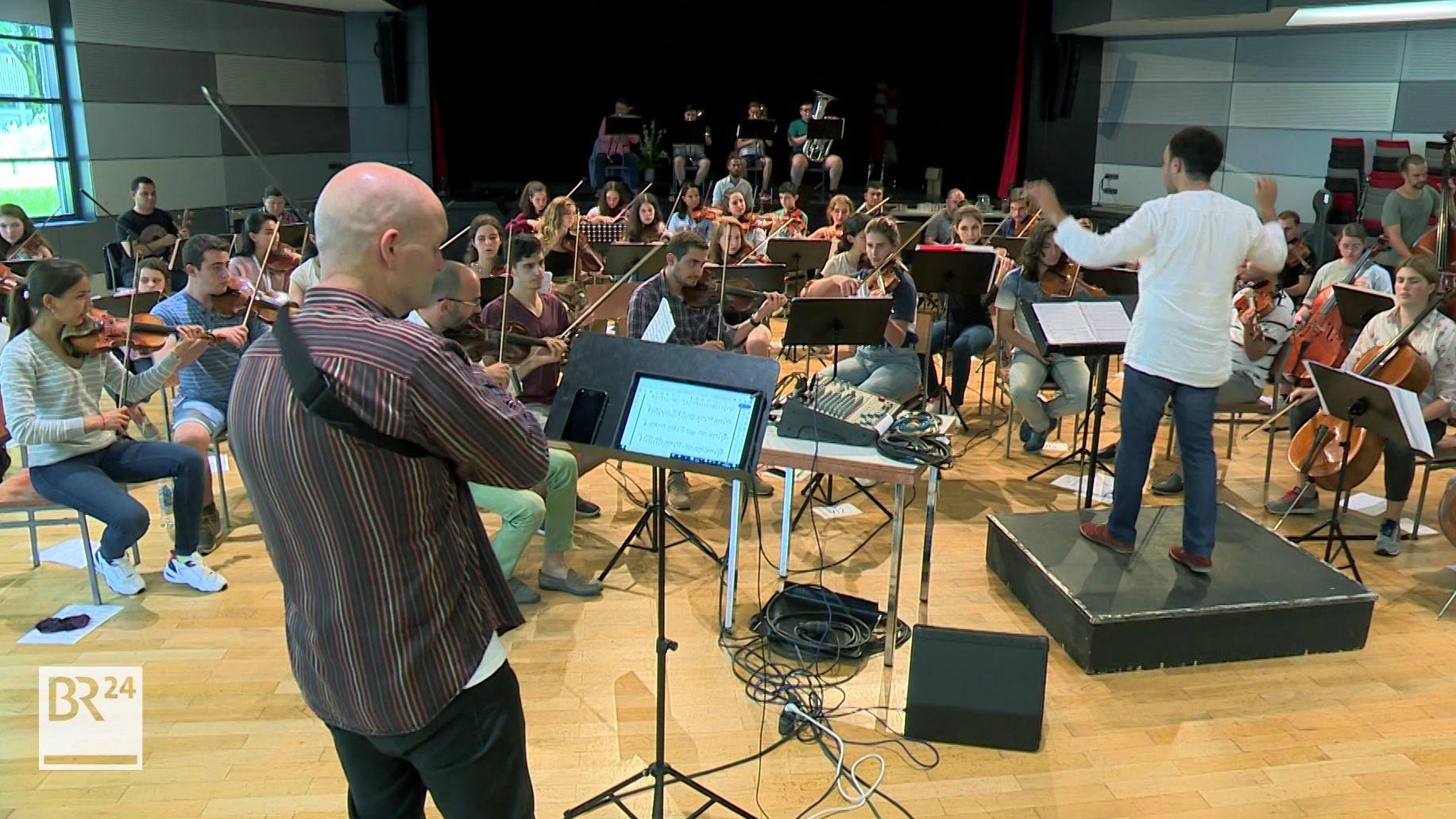 Ein Dirigent probt mit Nachwuchsmusikern