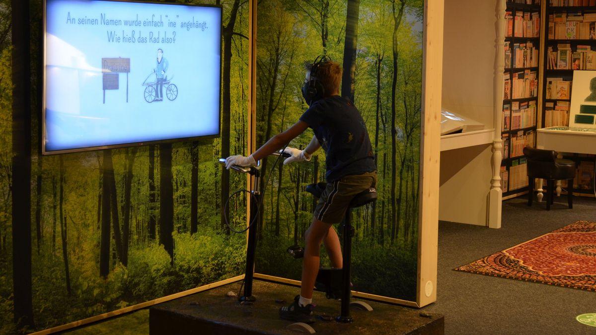 Ein Junge auf einem Fahrrad vor einem Bildschirm