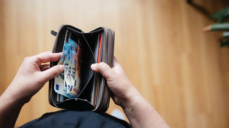 Eine Person hält eine geöffnete Geldbörse in Händen - darin befinden sich einige Euroscheine. (Symbolbild)