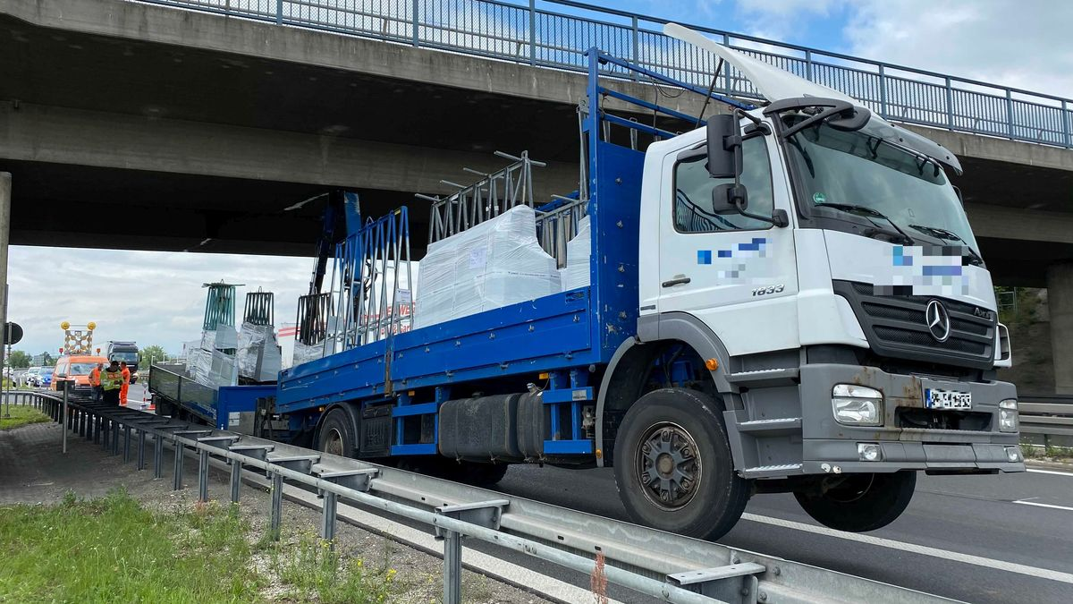 Der blau-weiße Lastkraftwagen steckt mit seinem Kran an einer Autobahnbrücke auf der A70 fest. Die Vorderräder hängen in der Luft.