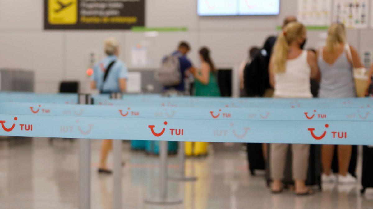 Urlaubsreisende stehen an einem Tui-Schalter an einem Flughafen und warten auf ihre Abreise.