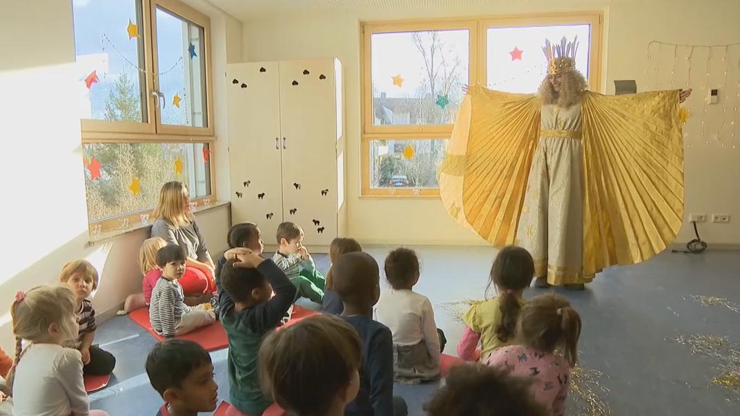 Das Christkind Benigna Munsi breitet vor den Kindern der Kindertagesstätte ihre Arme aus