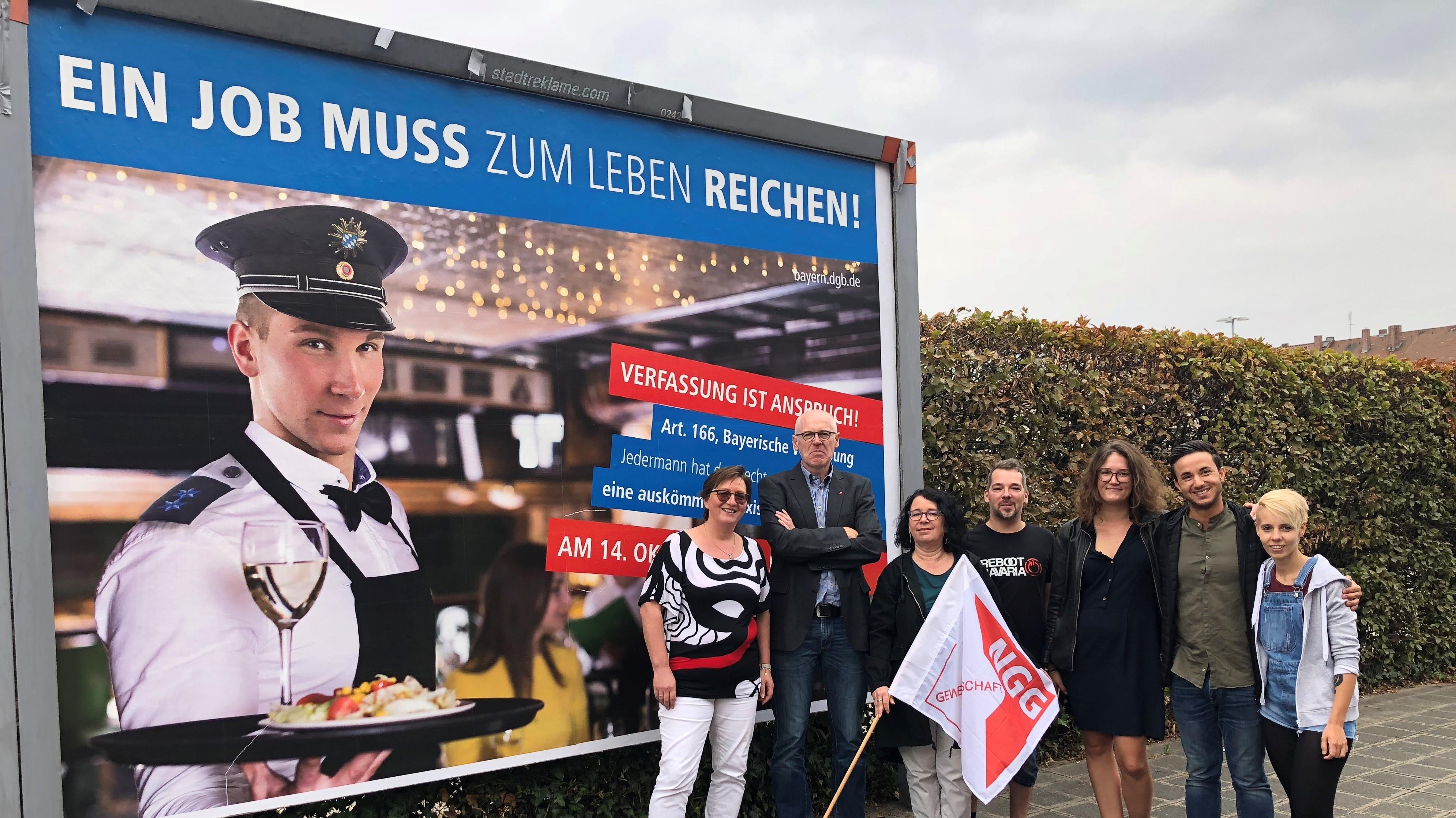 """Gewerkschafter stehen vor einem Plakat mit Schriftzug """"Ein Job muss zum Leben reichen!"""""""