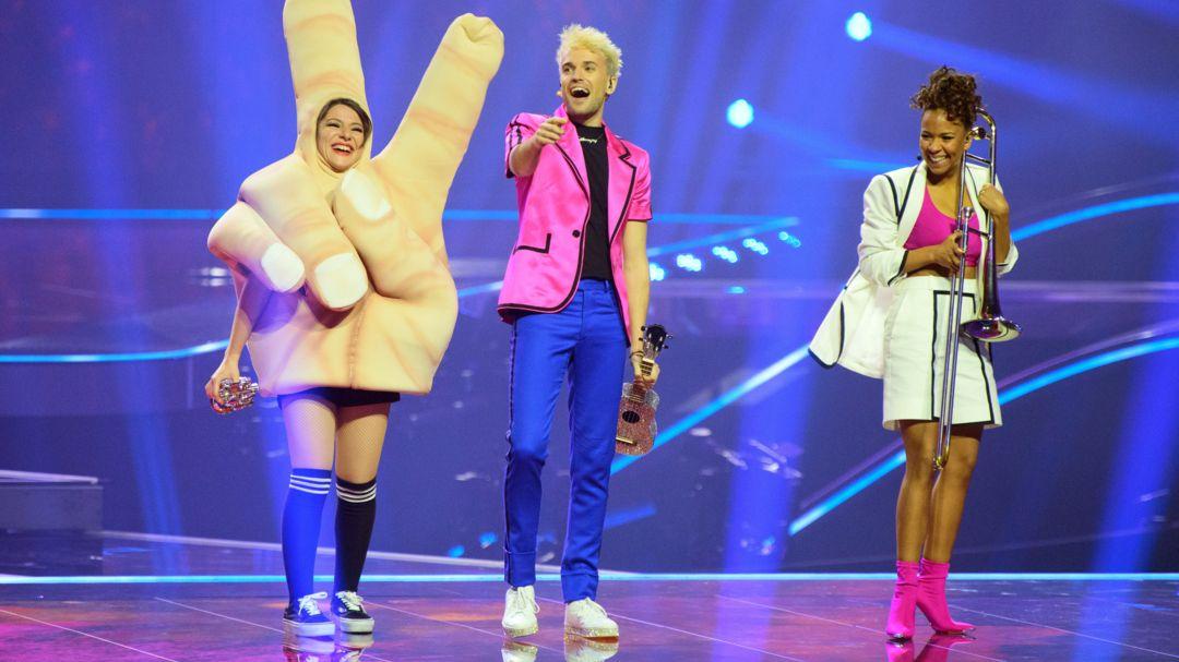 Drei Personen auf der Bühne, rechts eine Frau in Hand-Kostüm, dann in der Mitte ein Sänger, rechts eine Frau mit Posaune.