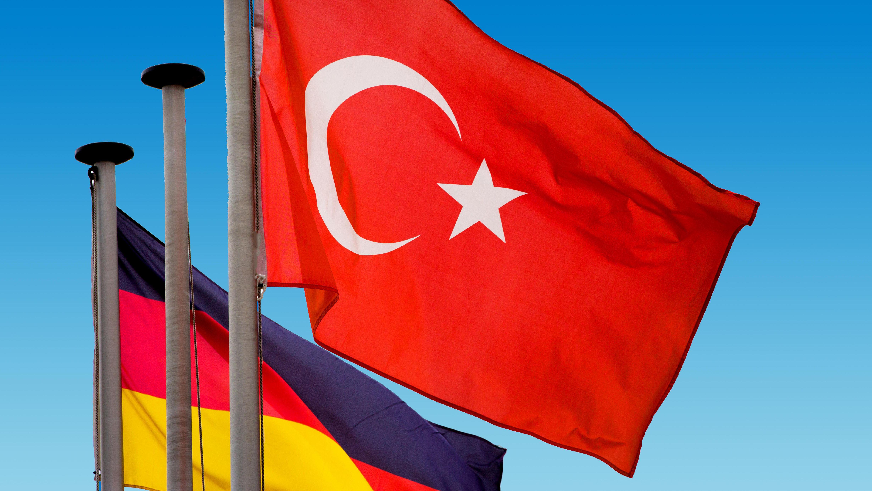 Türkische und deutsche Nationalflaggen wehen vor blauem Himmel.