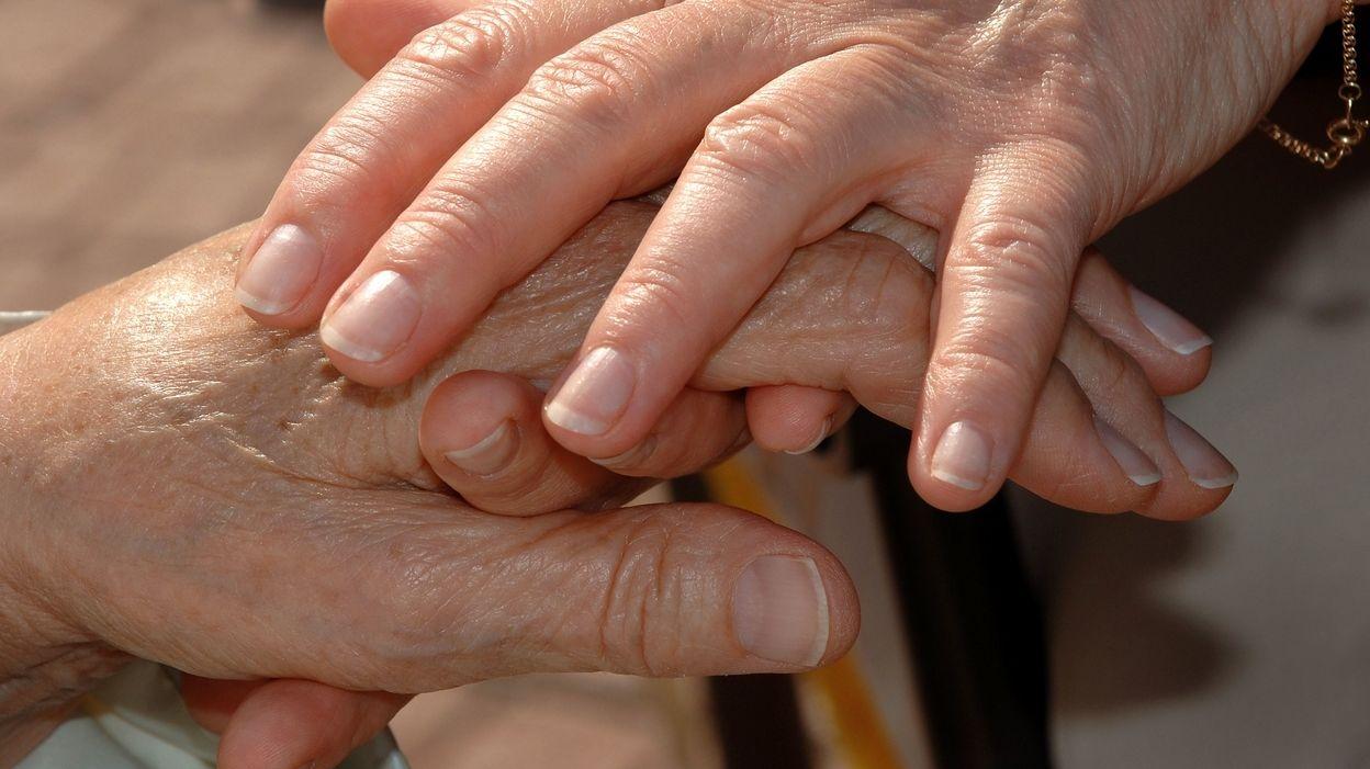 Zwei jüngere Hände umfassen eine ältere Hand.