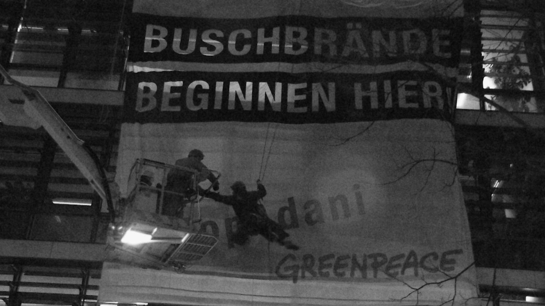 """An der Siemens-Konzernzentrale brachten Aktivisten von Greenpeace ein Transparent mit der Aufschrift """"Buschbrände beginnen hier"""" an."""