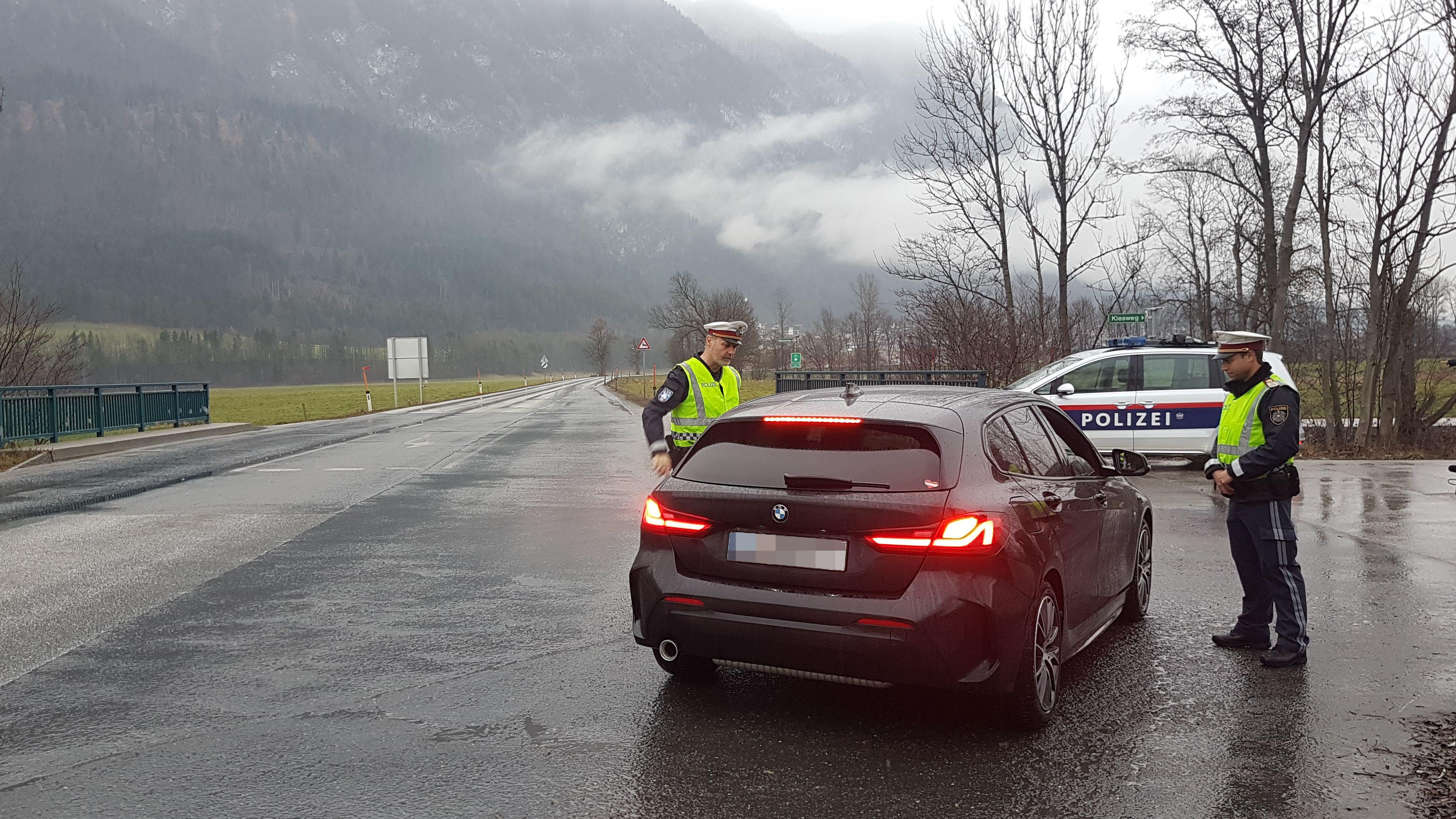 Zwei Polizeibeamte kontrollieren ein Fahrzeug auf einer tiroler Landstraße
