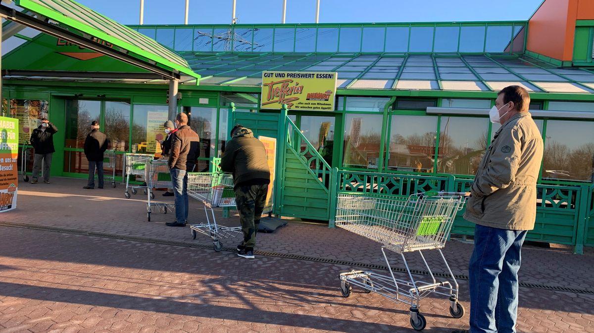 Kunden warten am Montagmorgen auf Einlass in den Baumarkt