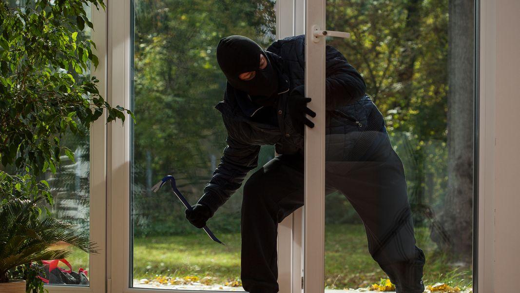 Ein Einbrecher mit dem Brecheisen dringt durch die Terassentür in ein Haus ein (Symbolbild)
