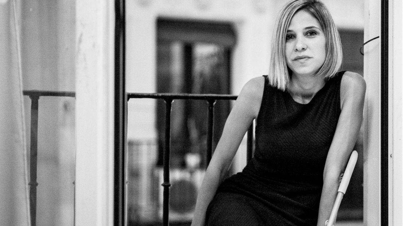 Die venezolanische Schriftstellerin Karina Sainz Borgo im schwarzen Kleid auf einem Stuhl