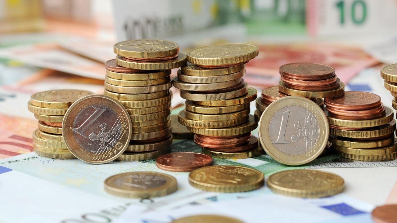 Euro-Müzen stapeln sich auf Geldscheinen.