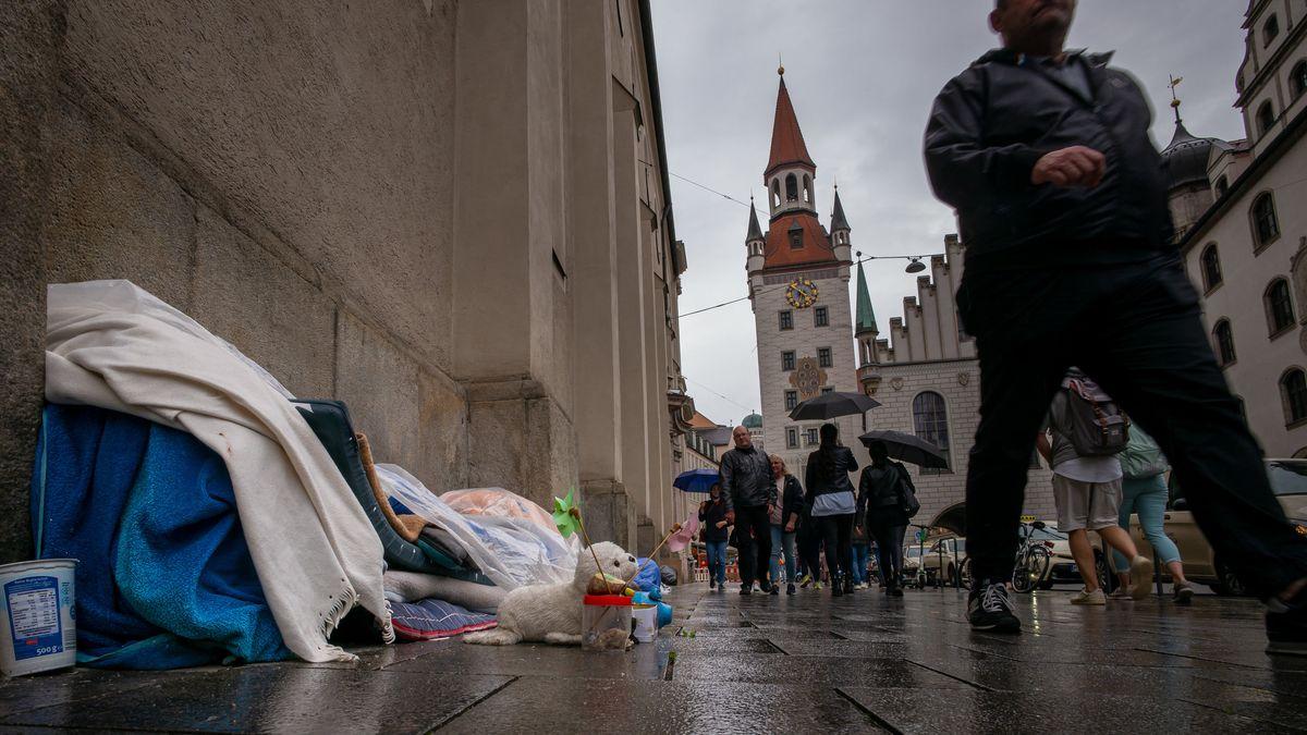 Bayern, München: Ein Obdachloser liegt in mehrere Decken und Planen eingehüllt auf dem Bürgersteig neben der Heiliggeistkirche.