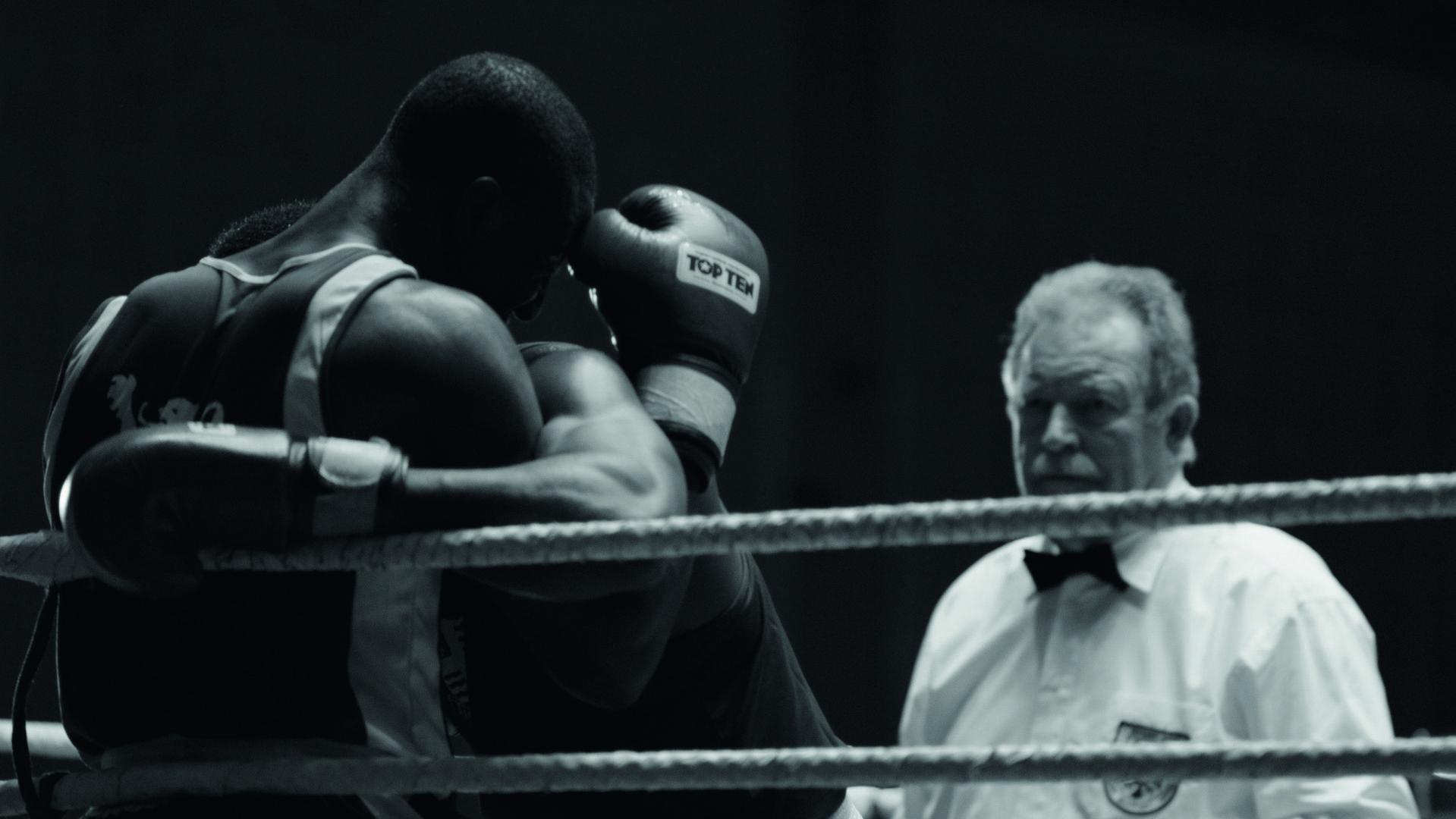 Zwei Boxer im Ring werden von einem Ringrichter in weißem Hemd beaobachtet
