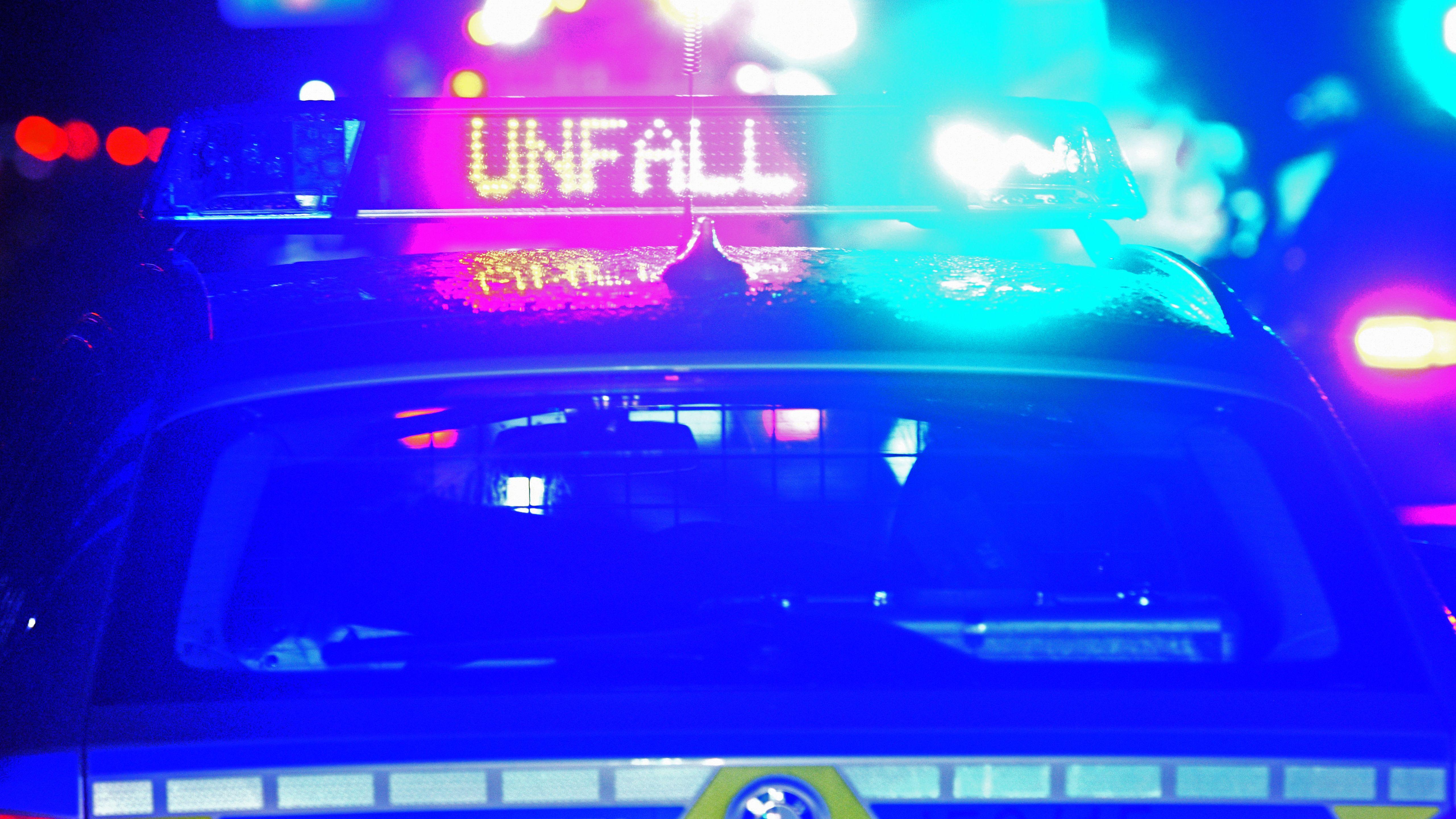 """Polizeifahrzeug im Dunkeln mit Blaulicht und mit rot-leuchtendem Hinweisschild """"Unfall"""""""