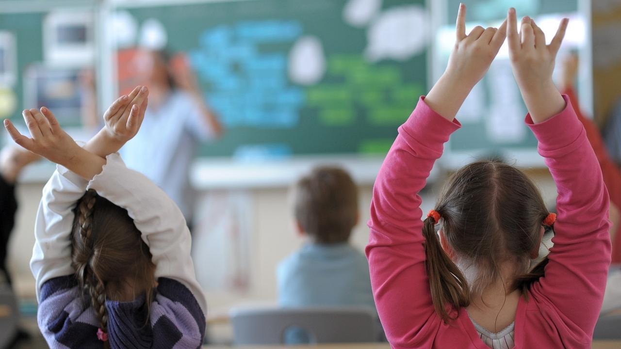 Zwei Schülerinnen melden sich während des Unterrichts in einem Klassenzimmer der Grundschule der Volksschule Burgebrach in Oberfranken.