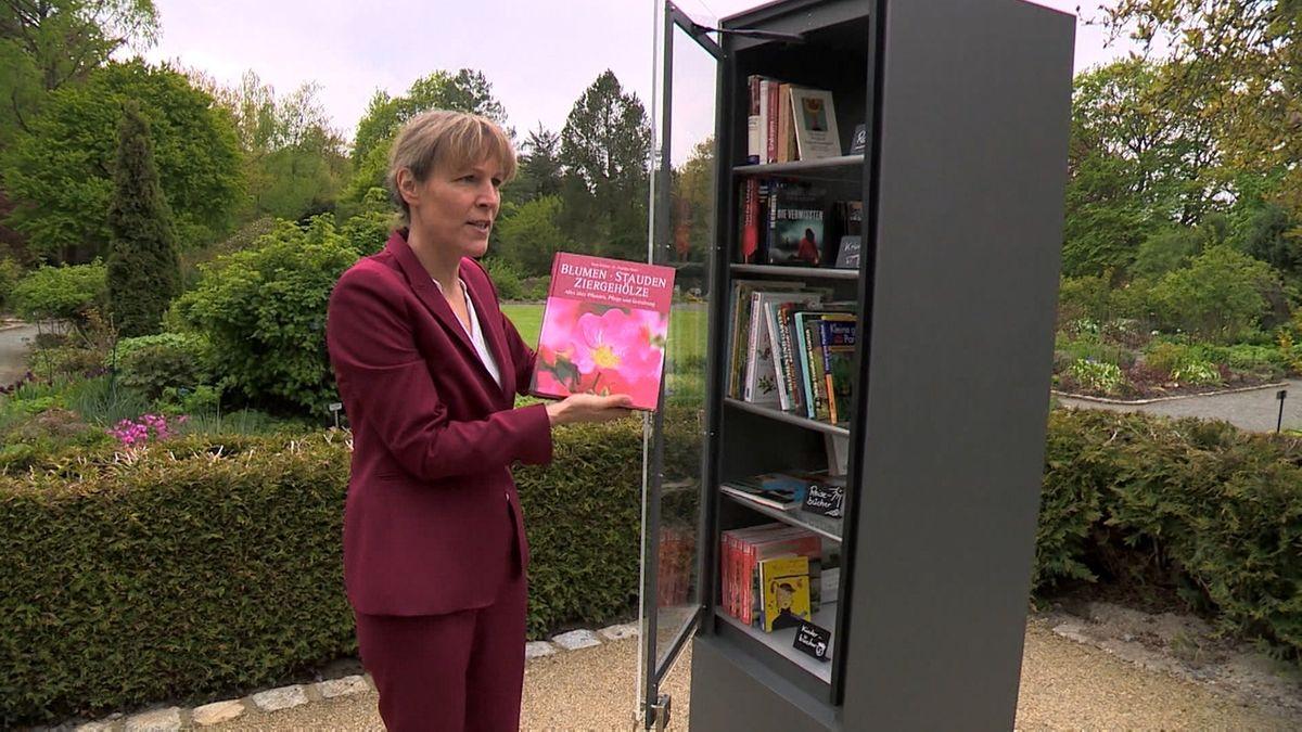 Die Hofer Oberbürgermeisterin Eva Döhla im roten Hosenanzug holt ein Buch aus dem Bücherschrank, der im Botanischen Garten steht.