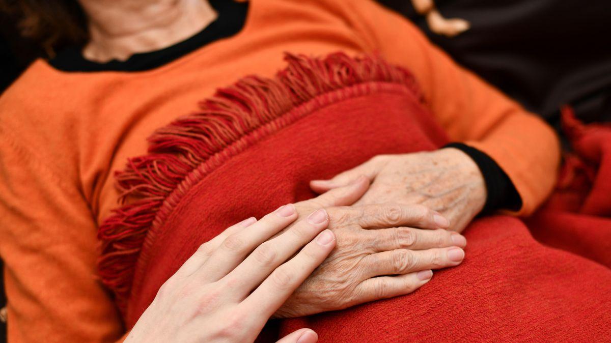 Auf den verschränkten Händen einer alten Frau ruht eine jung aussehende Hand.