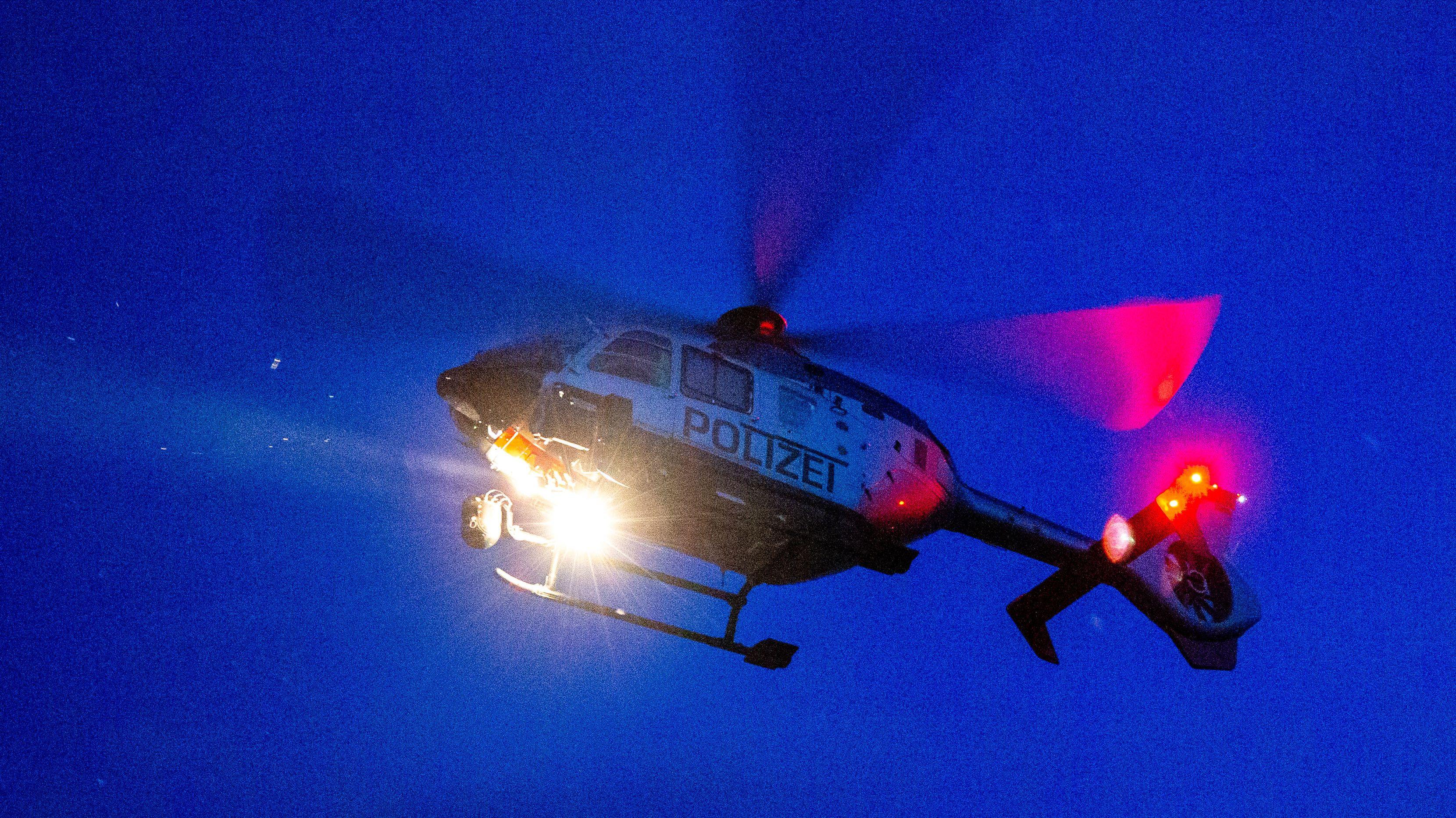 Ein Hubschrauber der Polizei sucht  den Boden mit einer Wärmebildkamera nach Personen ab.