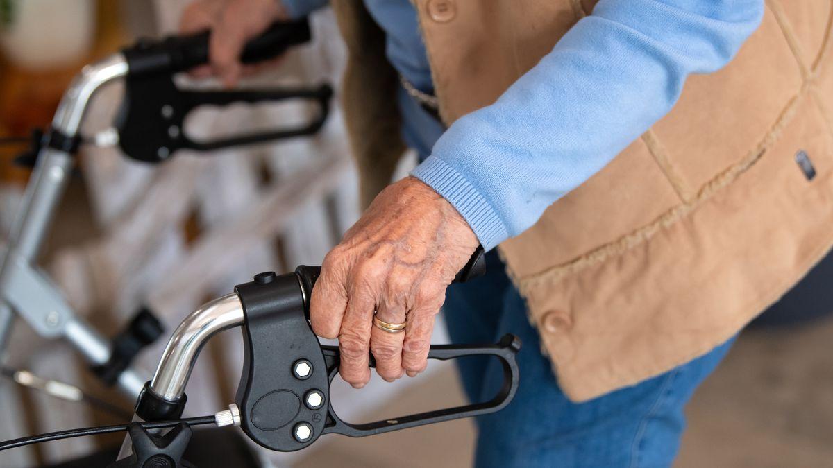 Eine Bewohnerin eines Altenheims geht mit ihrem Rollator über einen Flur