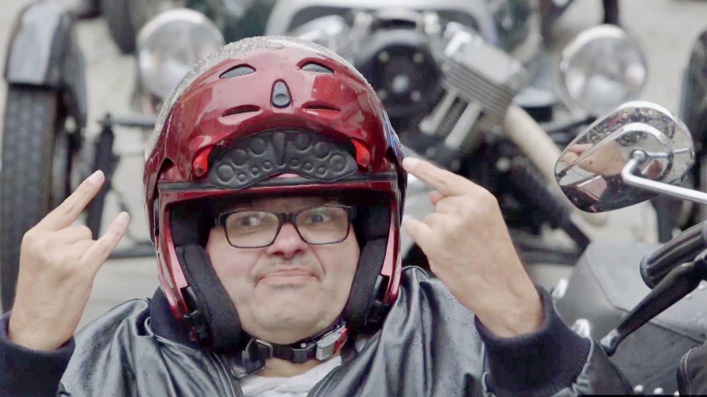 Ein Mann sitzt im Sozius eines Motorrads