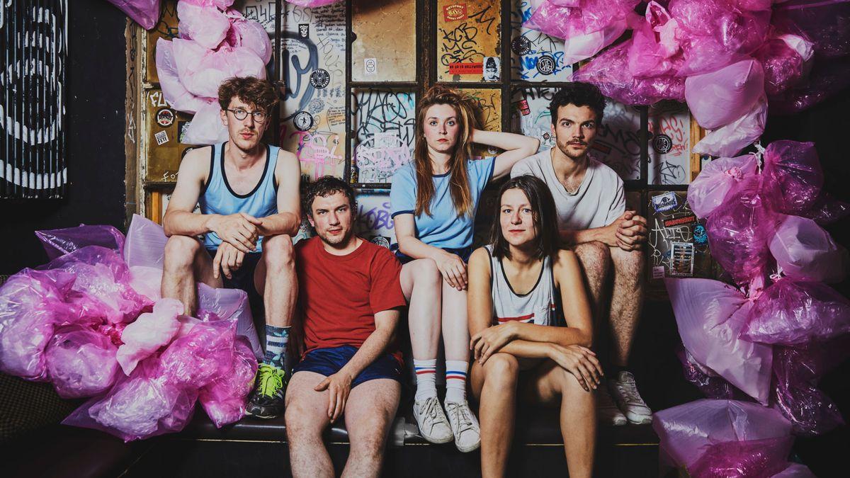 2 junge Frauen, 3 Junge Männer in Freizeit-Sportkleidung in trashiger Umgebung mit pinken Plastikbeuteln: Sorry3000