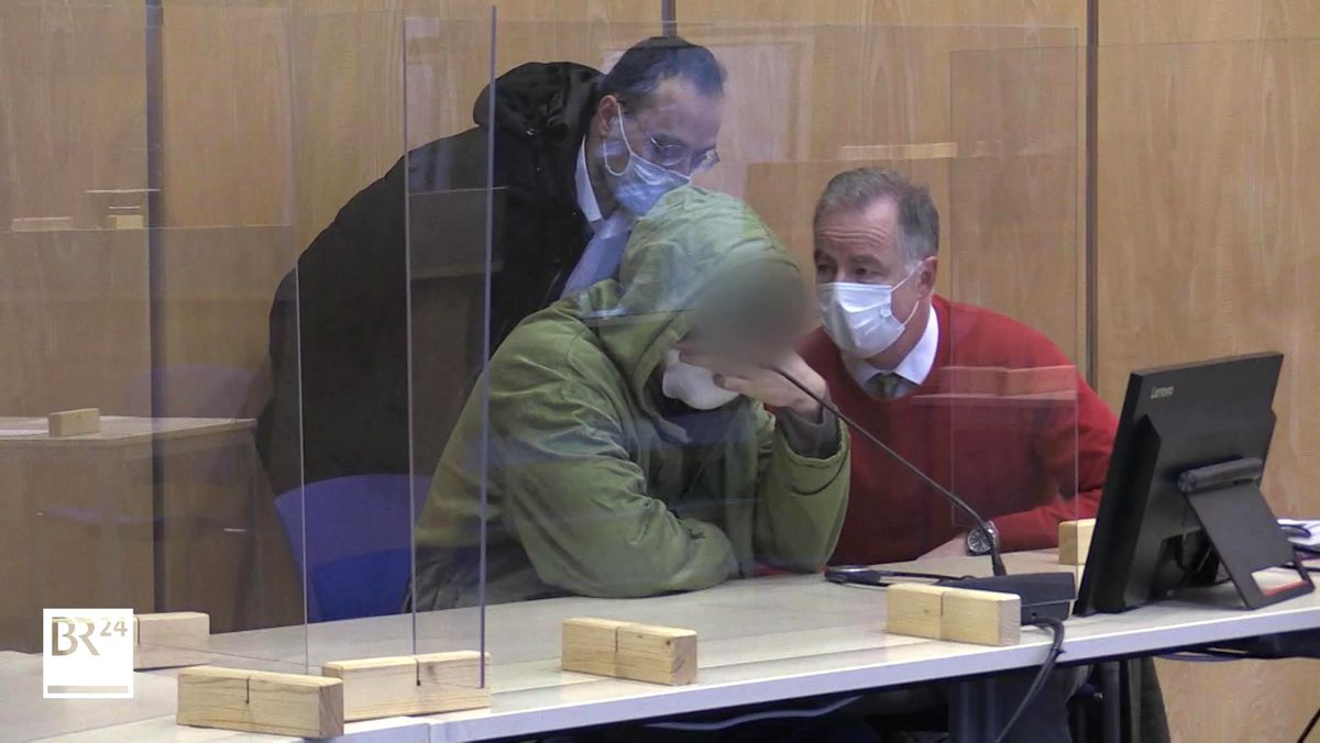 Der Angeklagte und zwei weitere Männer mit Mund-Nasen-Schutz beim Prozessauftakt.