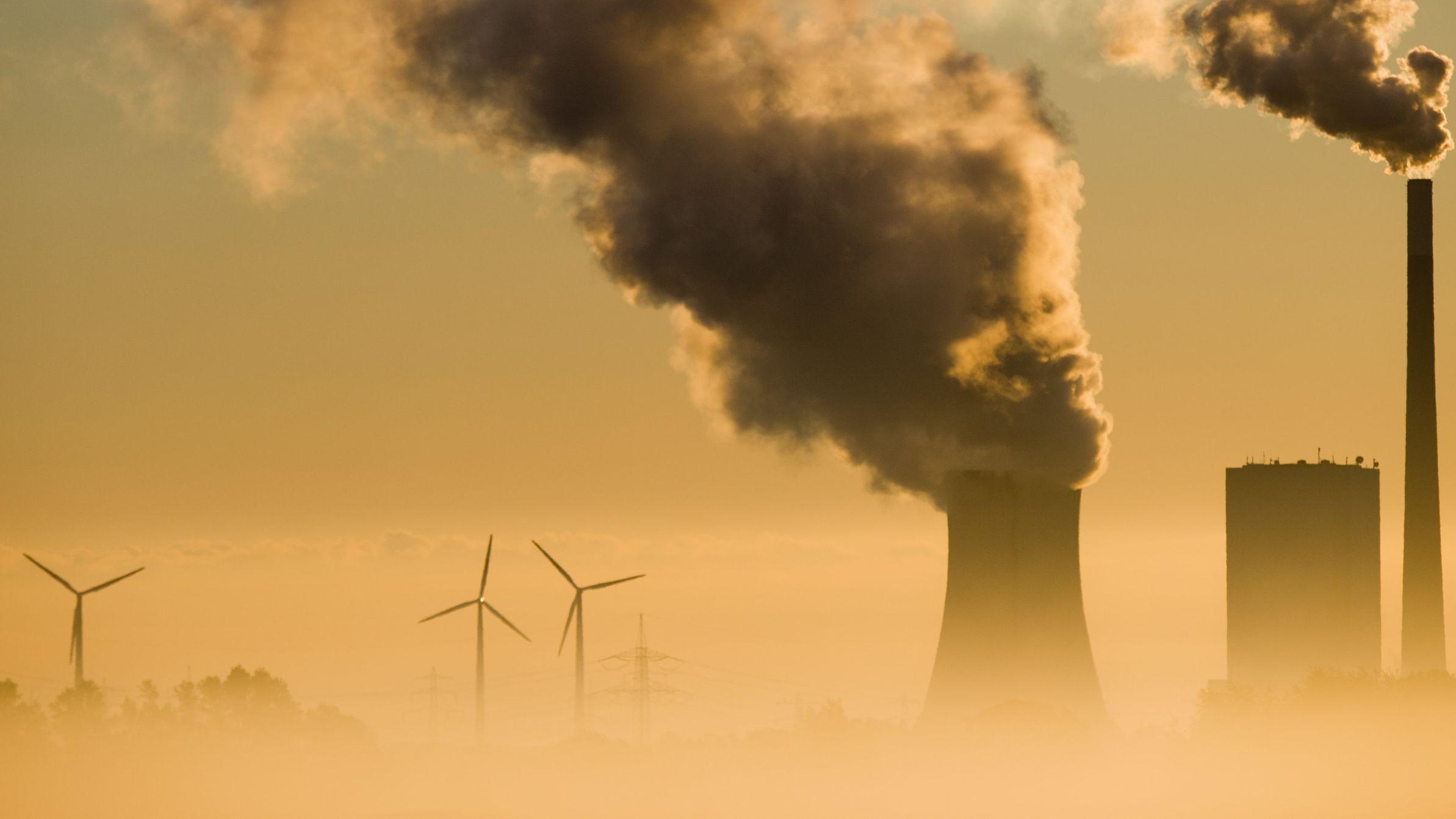 Kohlekraftwerke und Windräder im Smog