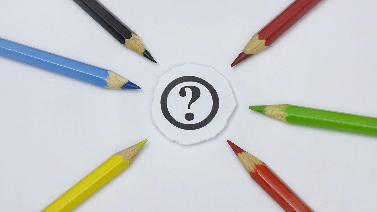 Verschiedene Buntstifte zeigen auf ein Fragezeichen (Symbolbild)