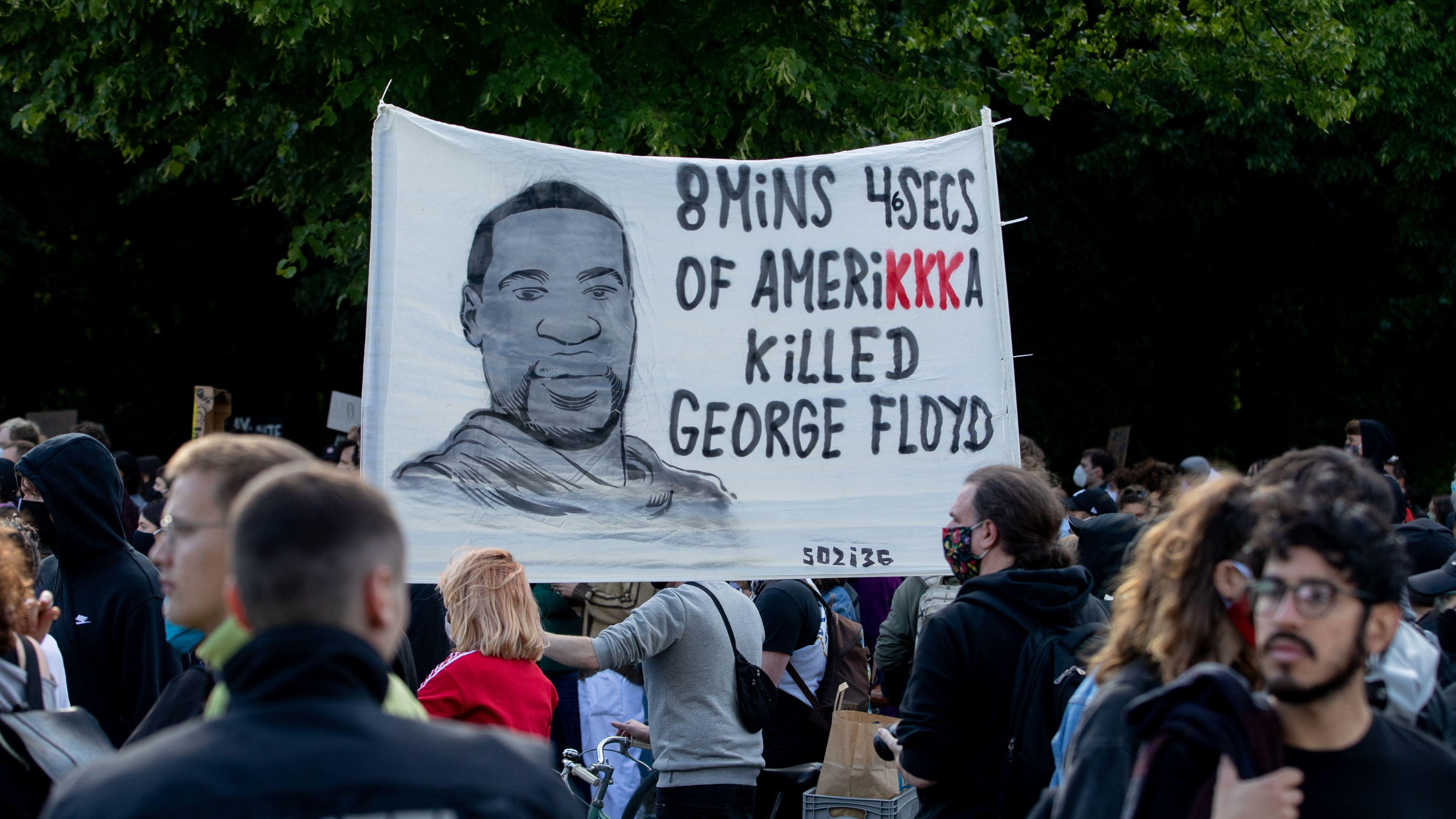 Ein Plakat mit dem Gesicht von George Floyd wird bei einer Kundgebung vor der US-Botschaft gegen den gewaltsamen Tod des Afroamerikaners durch einen weißen Polizisten in die Höhe gehalten.