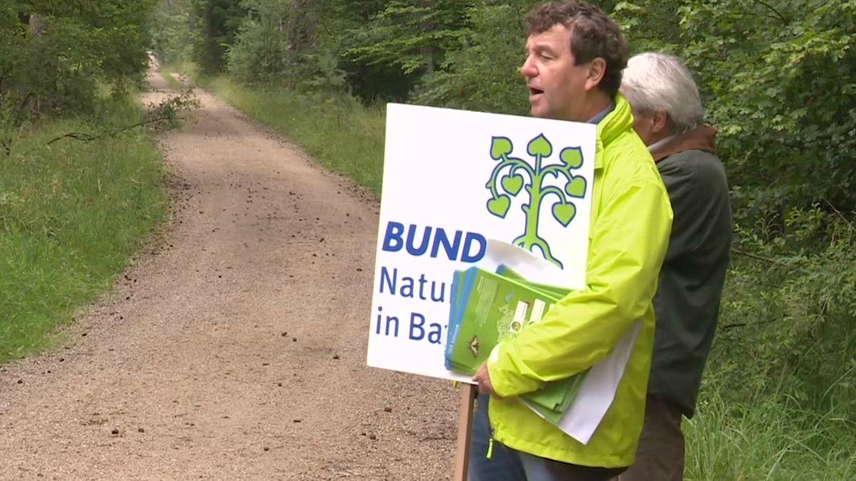"""Mann im Wald mit Schild """"Bund Naturschutz in Bayern"""""""