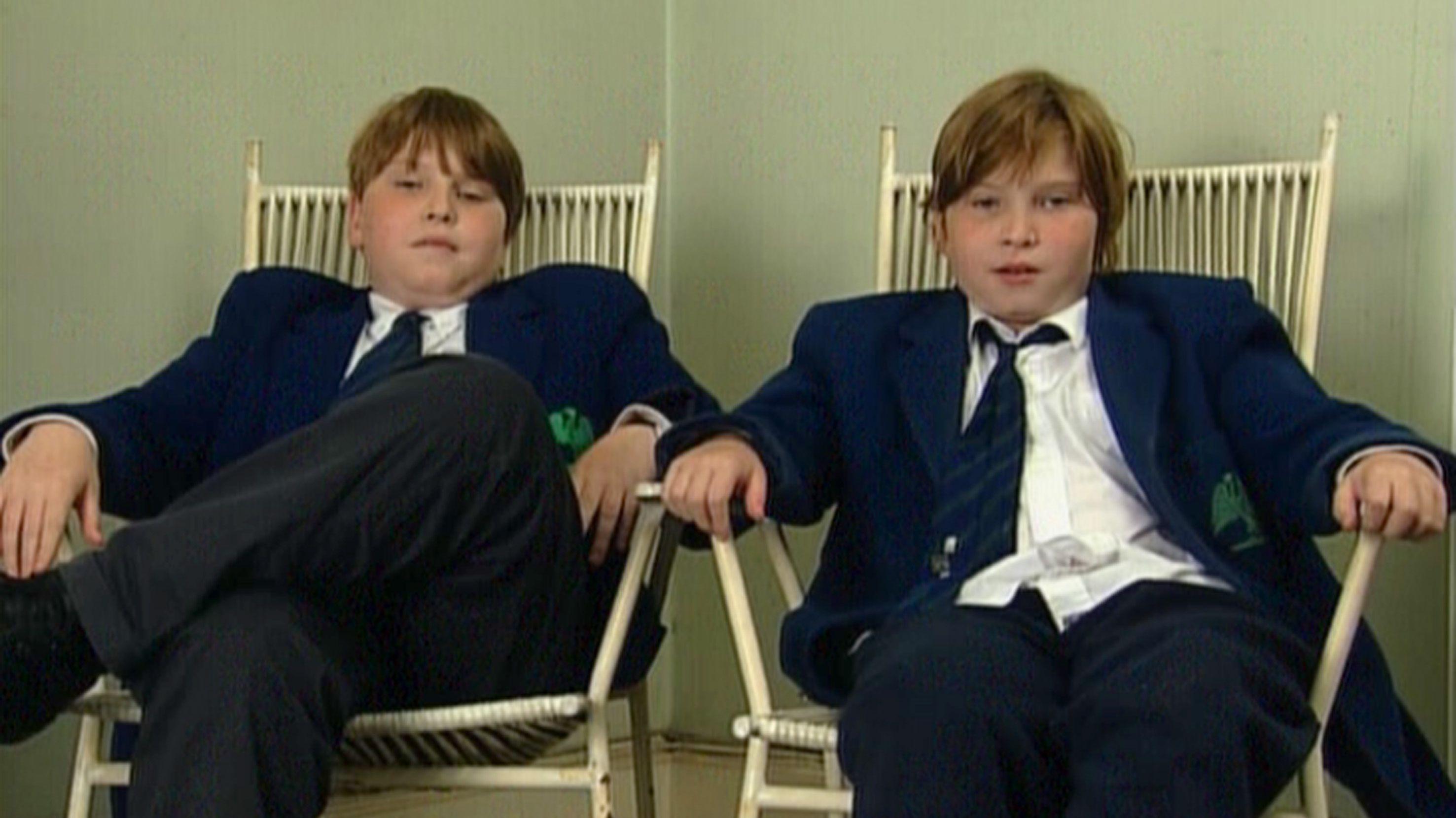 Zwillingsbrüder sitzen in blauen Anzügen nebeneinander in weißen Holzstühlen. Der linke ist ordentlich, der rechte hat zersauste Haare, das Hemd aus der Hose und die Krawatte gelockert.