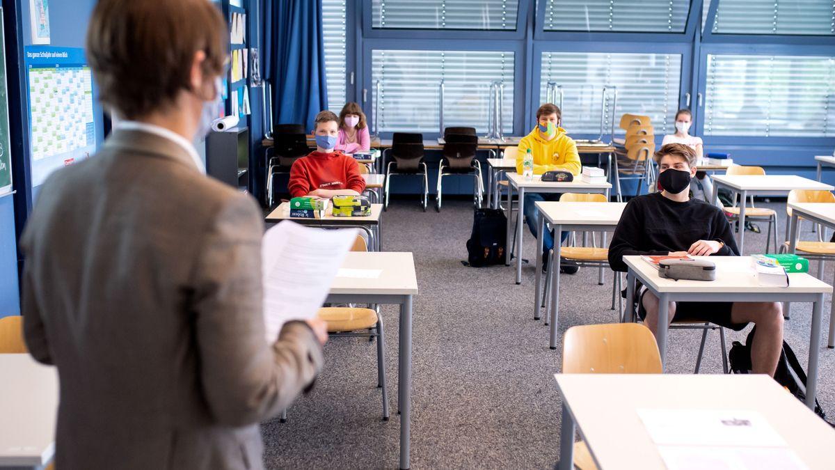 Schüler sitzen mit Maske und Abstand in einem Klassenzimmer