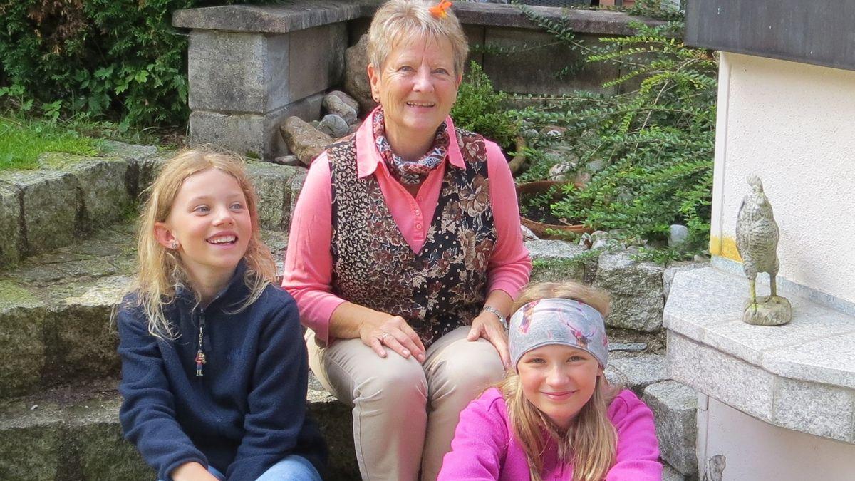 Bärbel Steinbacher sitzt mit den beiden Mädchen auf einer Steintreppe.