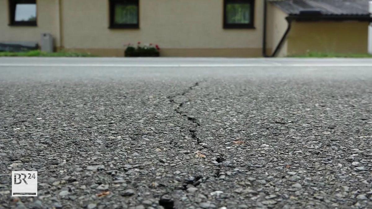 Ein Riss zieht sich quer über eine Teerstraße, dahinter die Fassade eines Hauses.