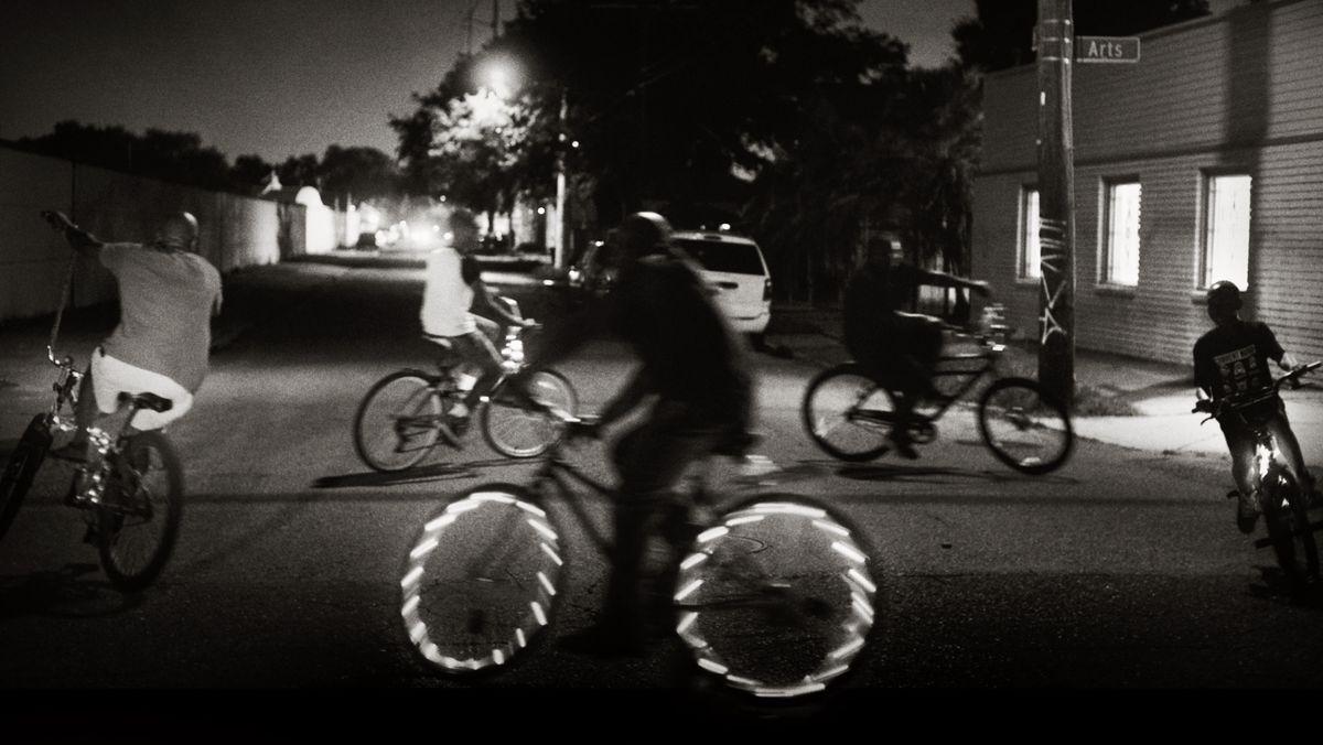 """5 schwarze Jungs radeln nachts auf einer Straße im Kreis, einer von ihnen hat beleuchtete Speichen: Szene aus """"What You Gonna Do When The World's On Fire?"""""""