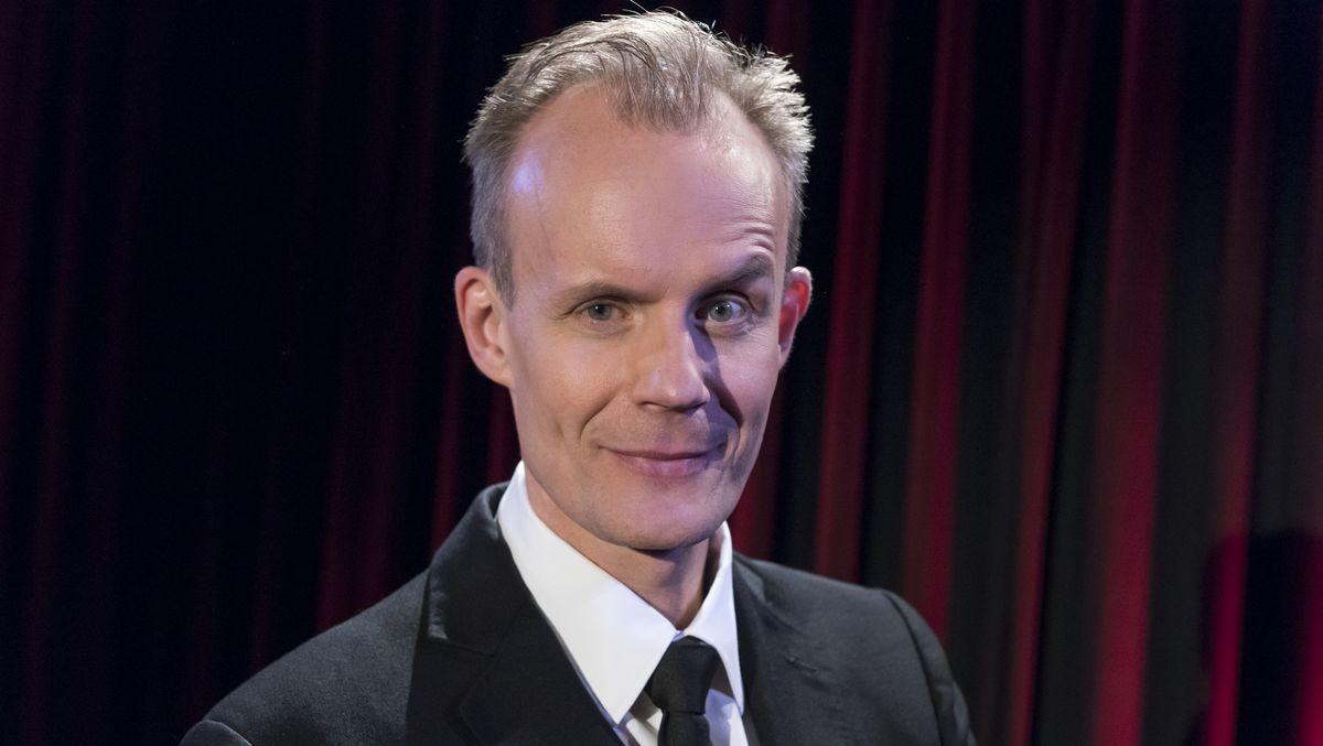 Max Uthoff blickt vor einem roten Vorhang stehen mit hochgezogener Augenbraue in die Kamera