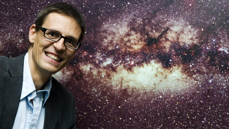 Der Schweizer Astrophysiker Didier Queloz posiert vor dem Bild der Milchstraße am Genfer Observatorium.