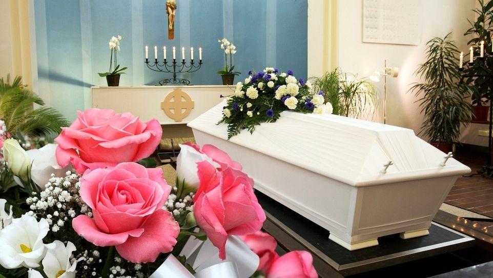 Bestattungsram mit Sarg und Blumen
