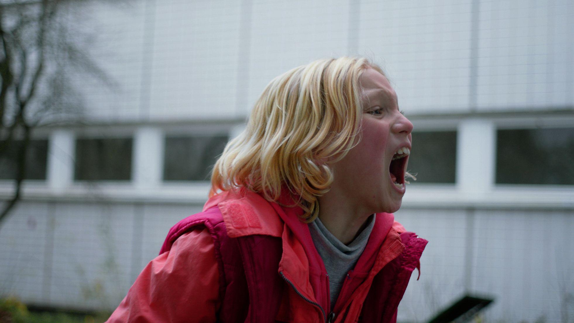 Schauspielerin Helena Zengel steht schreiend und mit hochrotem Kopf vor einem weißen Gebäude