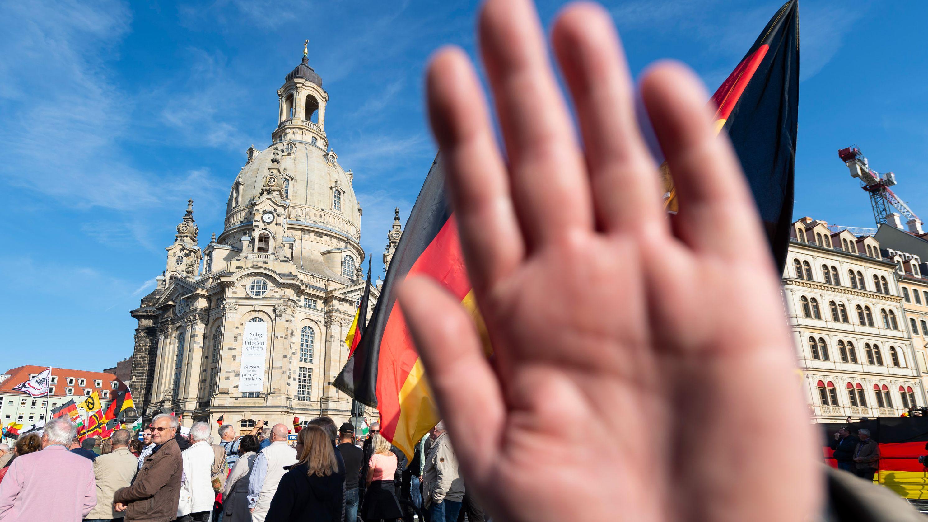 Ein Mann bei einer Pegida-Demonstration in Dresden hält die Hand in die Kamera.