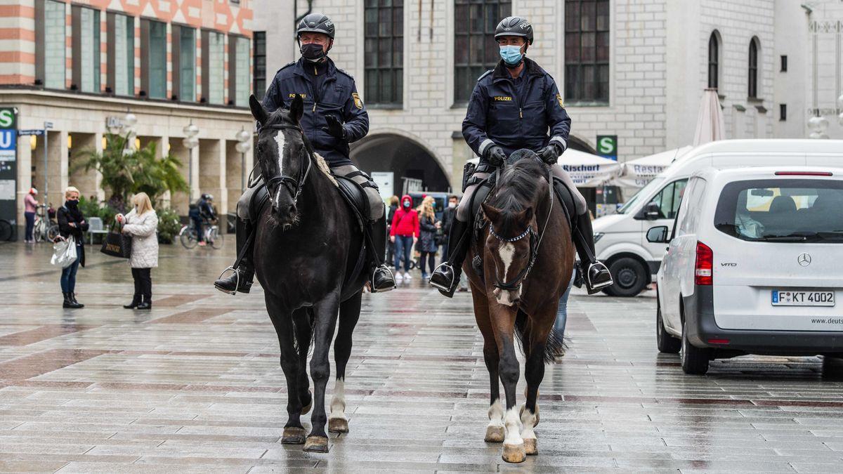 Zwei Polizisten reiten auf ihren Pferden über den Marienplatz, sie tragen Masken