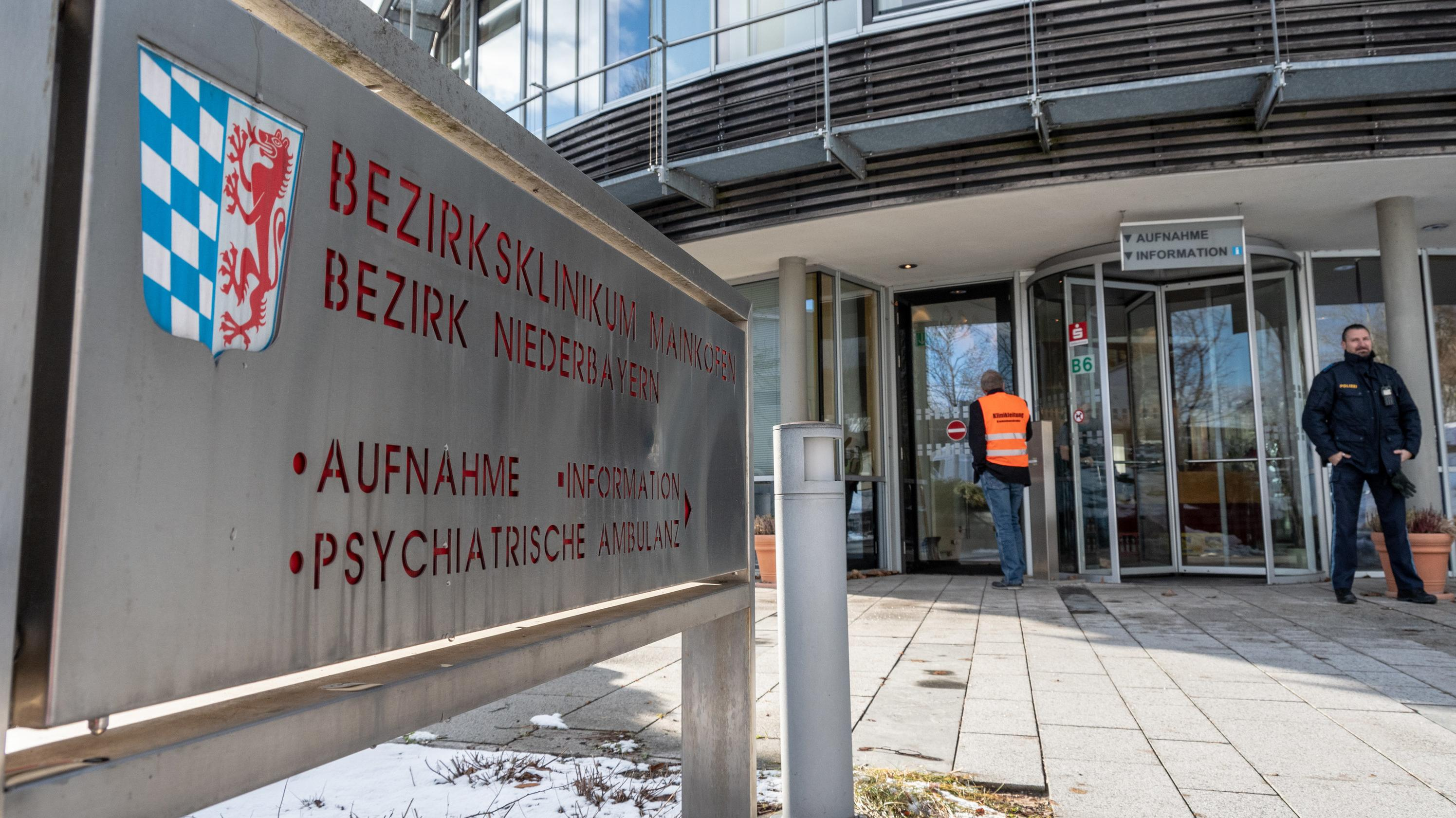 Ein Polizist steht vor dem Eingang des Bezirksklinikums Mainkofen (Lkr. Deggendorf)