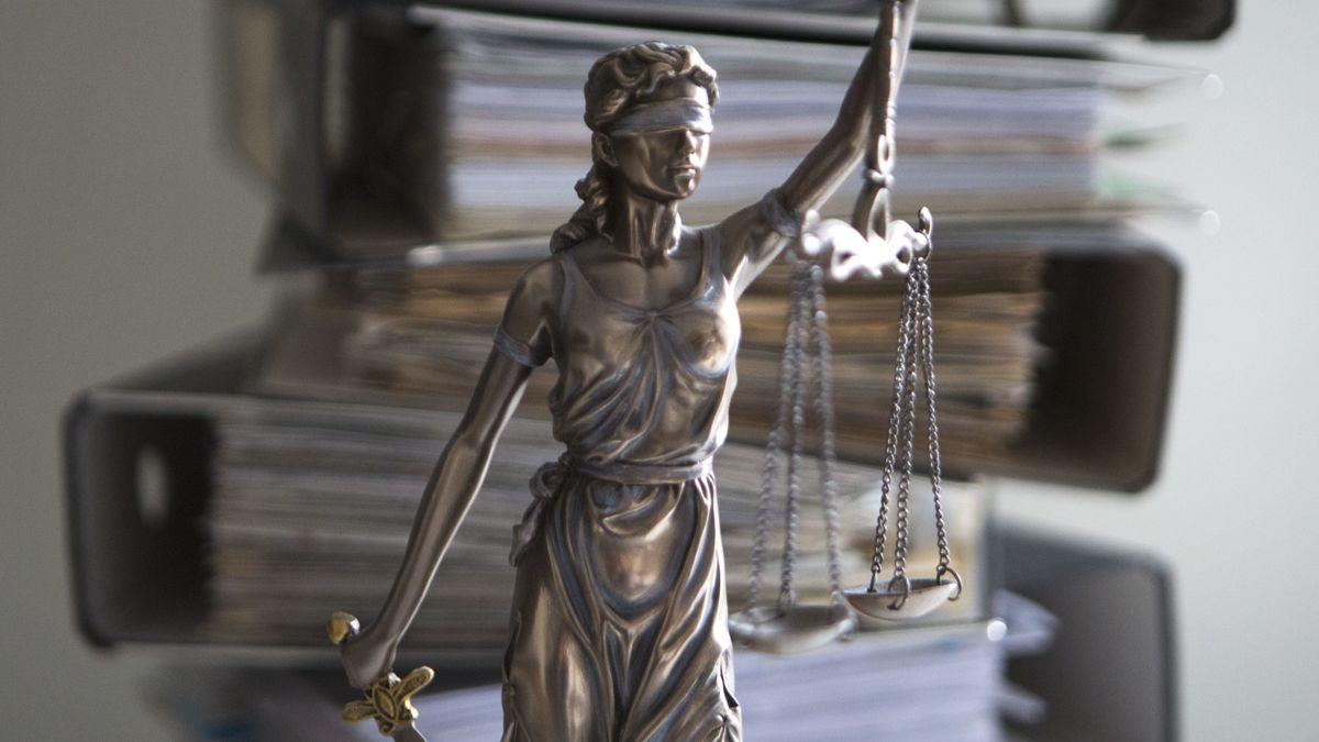 Justitia-Statue vor einem Stapel Akten