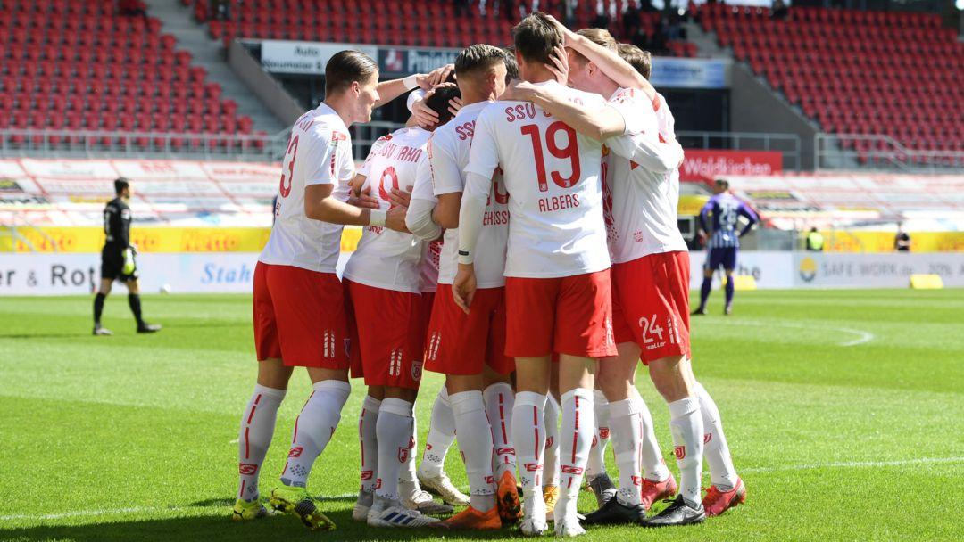 Spieler des SSV Jahn Regensburg liegen sich im Jahnstadion in den Armen.